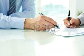 12620748-two-business-partners-signing-a-document